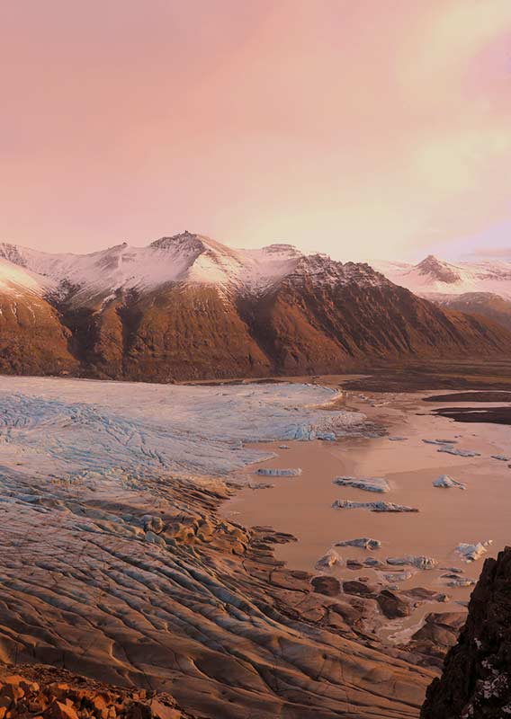 Large glacier flowing into a waterway, surrounded by mountains, viewed from above at sunset