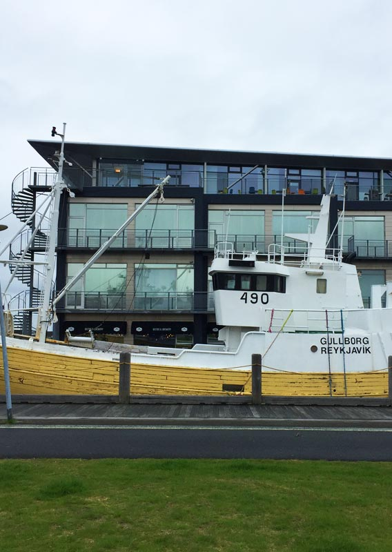 A yellow and white boat sat in a harbour next to a glass building