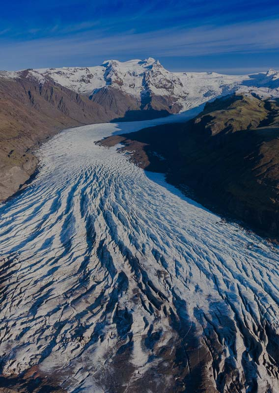 A glacier between tall mountains.