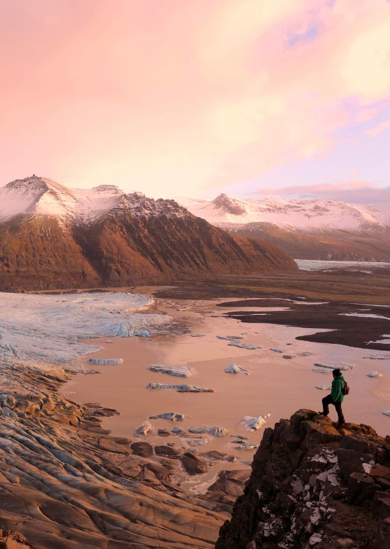 Hiker stands above calving glacier and mountain view at sunset