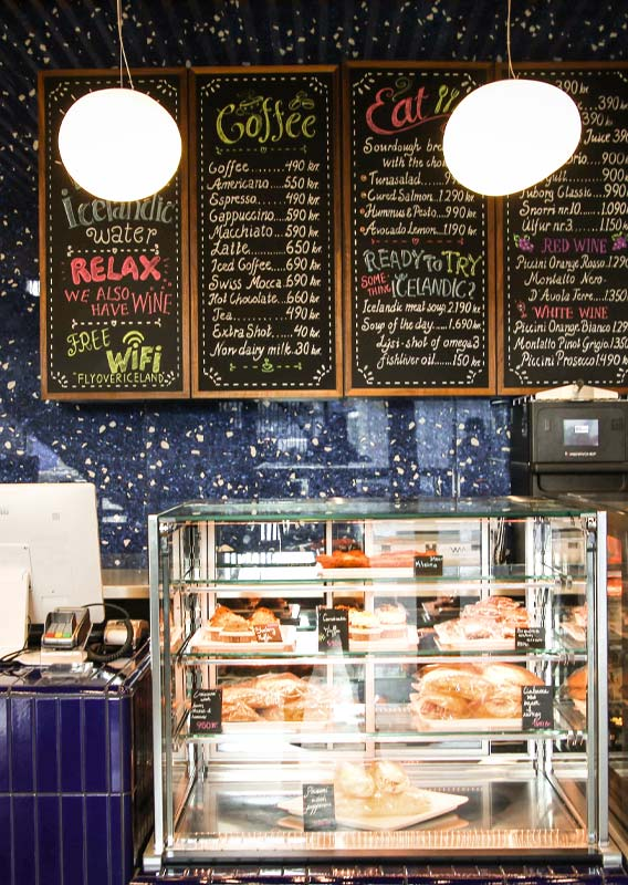 A cafe counter showing pastries and chalkboard menu