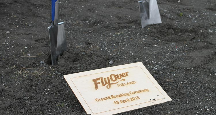 Shovels stick out of the ground at the FlyOver Iceland groundbreaking plaque.