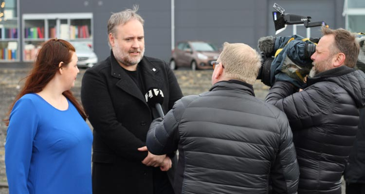 Two people are interviewed by a TV news reporter at the FlyOver Iceland groundbreaking ceremony.