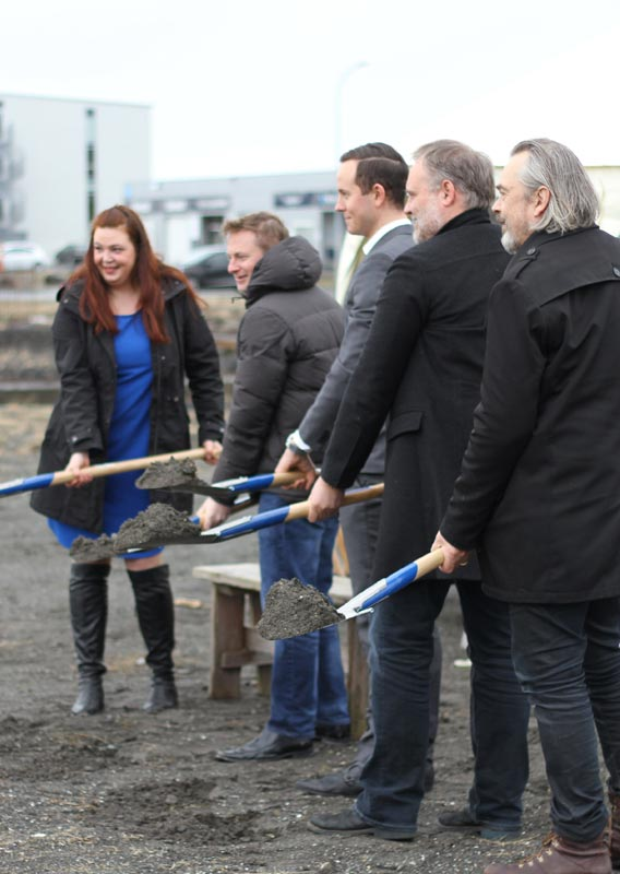 Five people stand with shovels of dirt at the FlyOver Iceland groundbreaking ceremony.