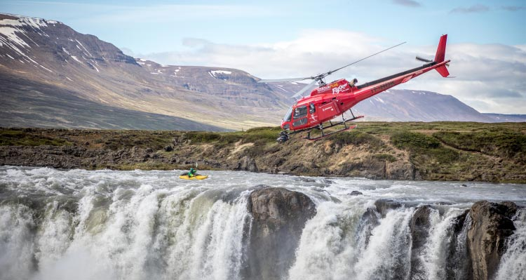 A helicopter flies above a kayaker approaching a waterfall descent.