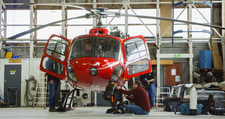 Workers fit the FlyOver Iceland helicopter in a hangar.