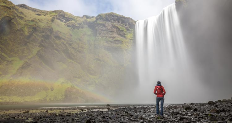 A person in a red jacket stands before a large waterfall.