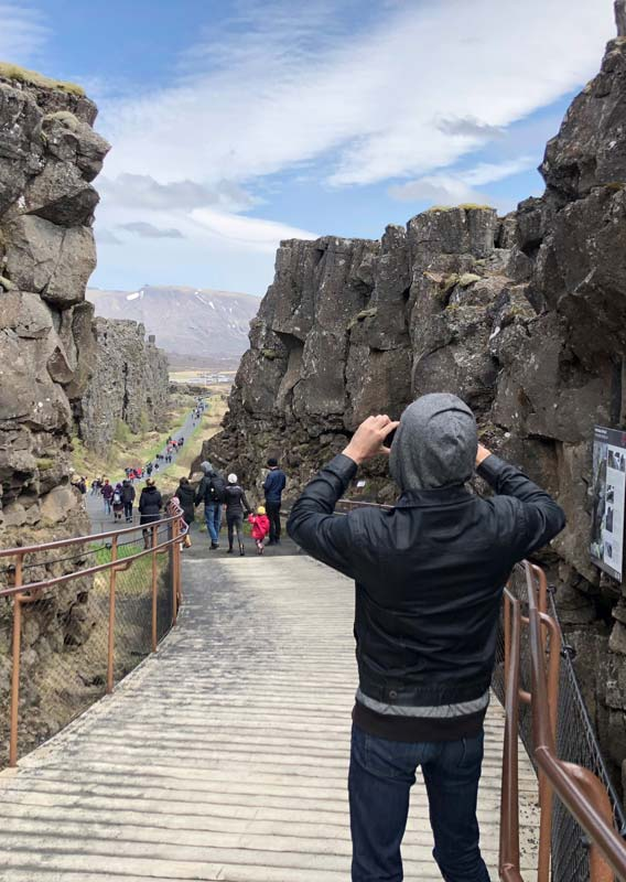 A tourist takes a photo of within a narrow rocky canyon.