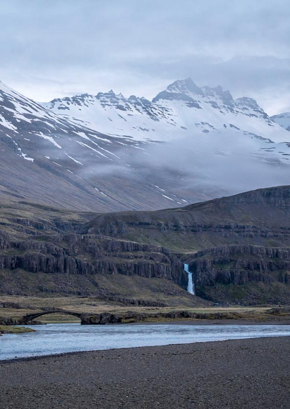 A waterfall descends towards a wide river below snow-covered mountains.