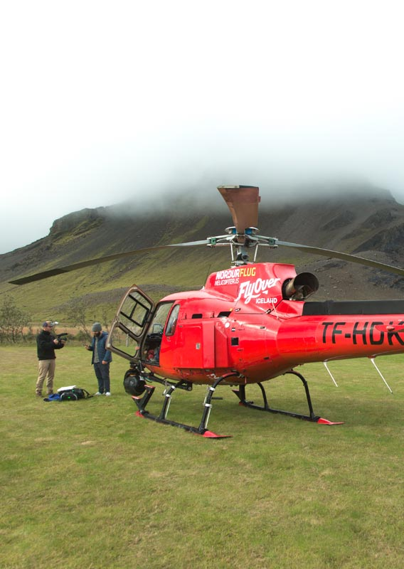 Two filmmakers stand next to a helicopter below a foggy mountain.