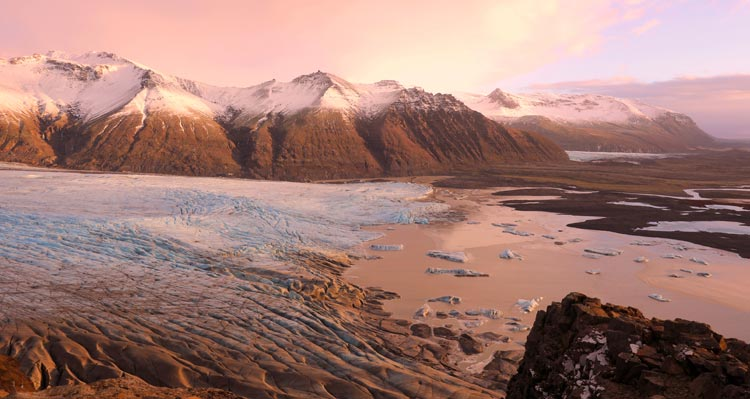 A glacier stretches below snow-capped mountains.