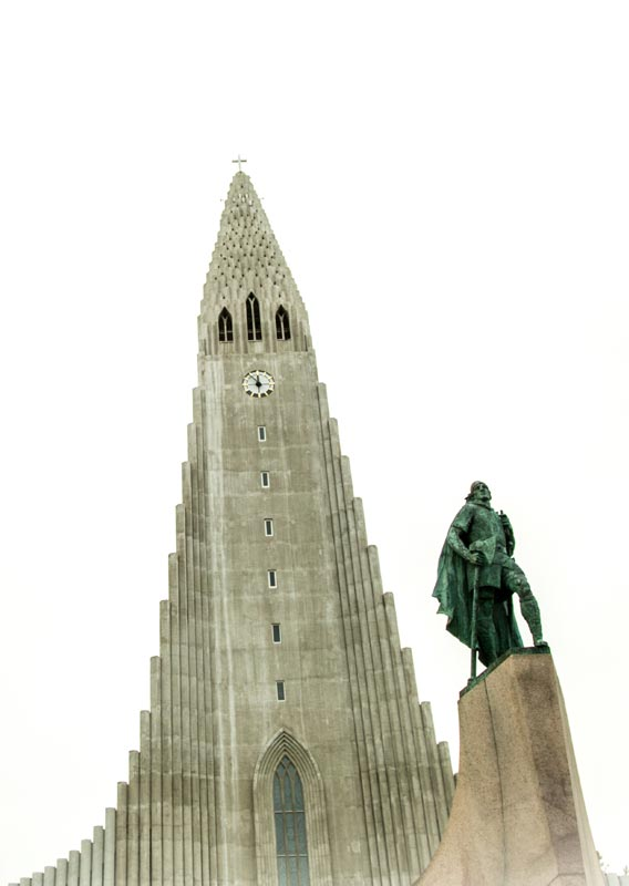 A statue of Leif Erikson in front of Hallgrímskirkja, a large stone cathedral.