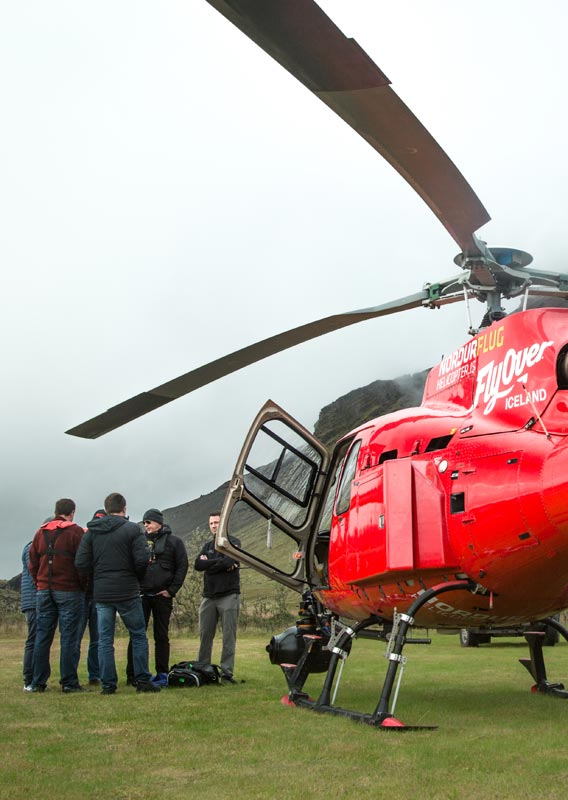 A film crew stands outside of a red helicopter under a low fog.