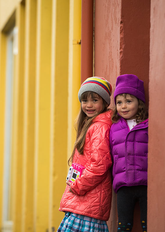 Two young girls pose among brightly coloured buildings of Reykjavík