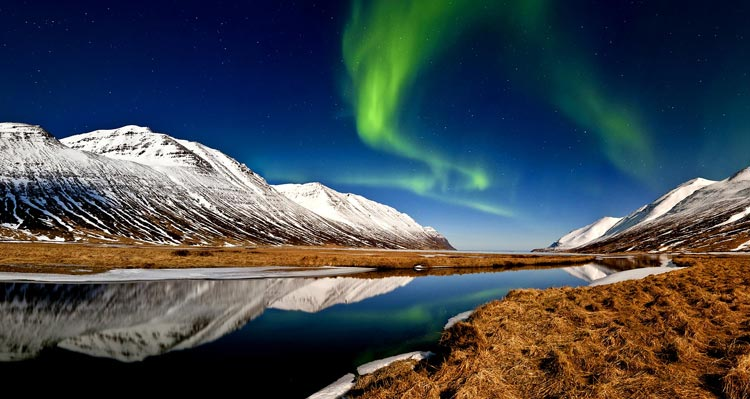 Green northern lights above snowy mountains and a river