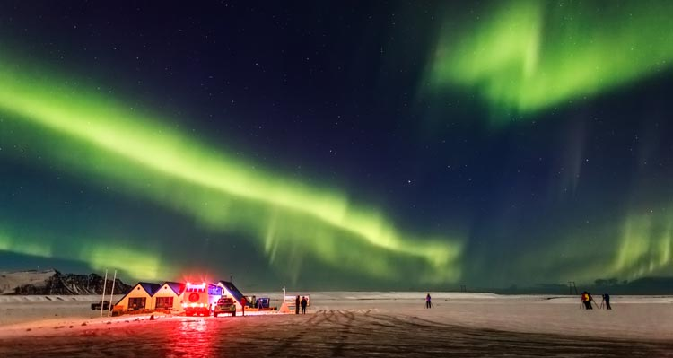 Green northern lights above a flat icy landscape and small buildings
