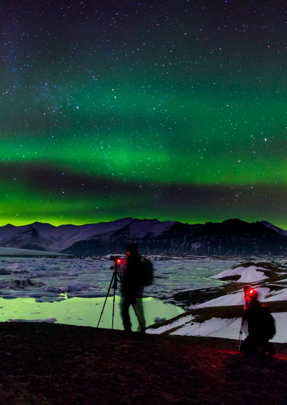 Two photographers set up their cameras under a night sky of green northern lights