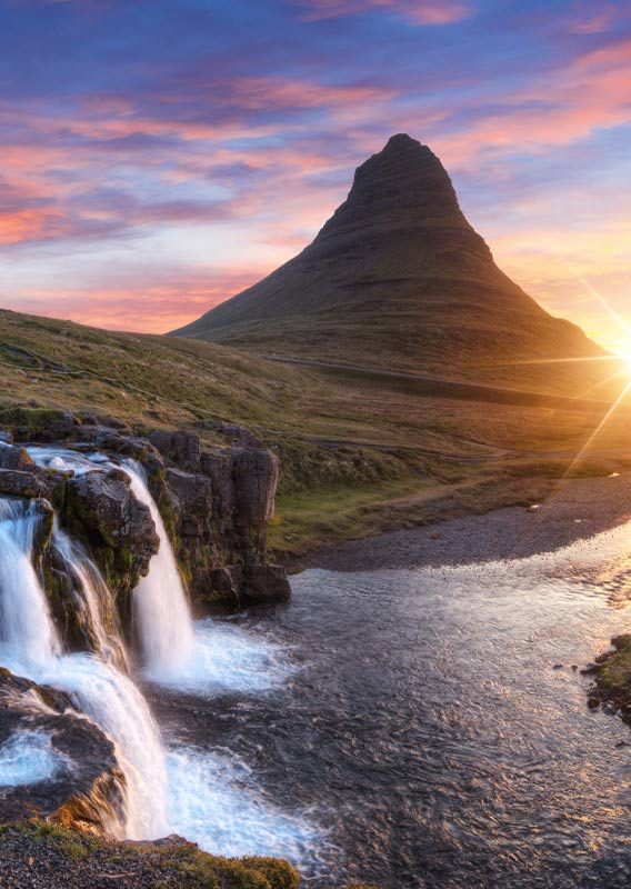 The Kirkjufellfoss waterfall in front of the mountain Kirkjufell.