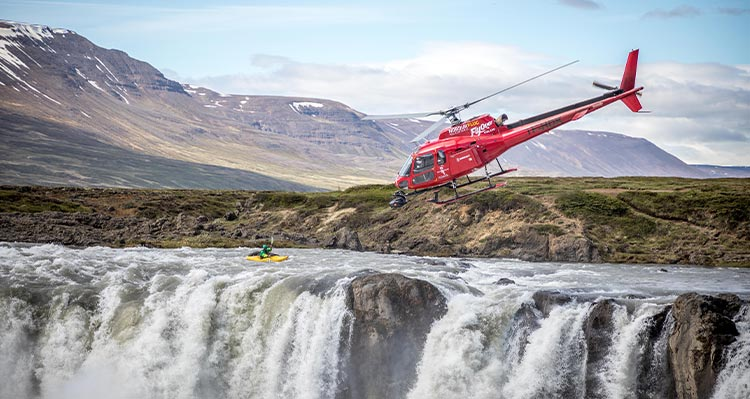 A kayaker on a river above a waterfall. A red helicopter flies nearby.