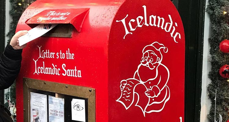A letter being put into a mailbox for Santa