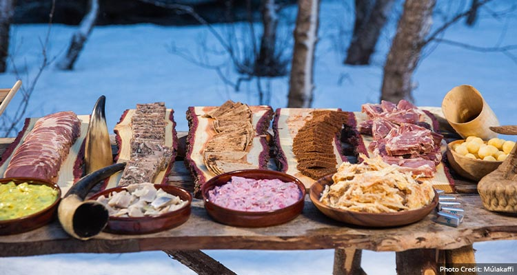 A platter of food on a table in a forest.