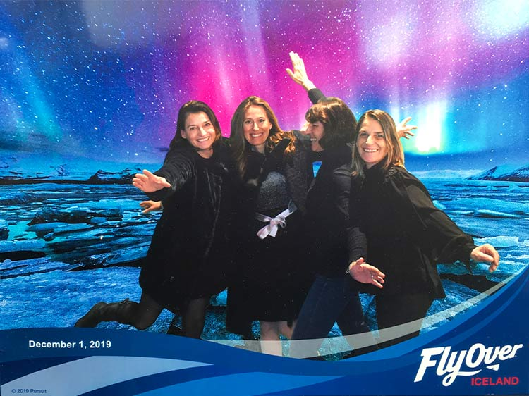 A group of people pose for a photo in front of a northern lights backdrop.
