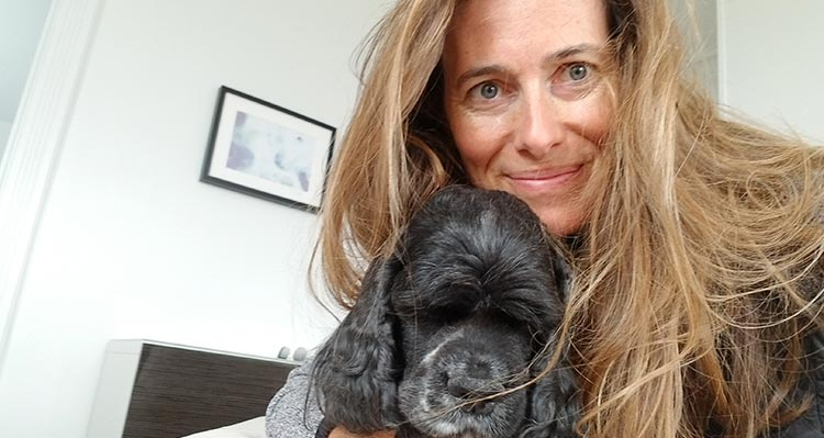 A woman holds a black dog close to her face.