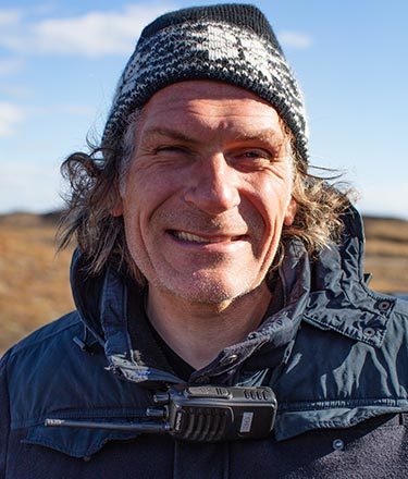 A man with scraggly hair under a winter hat.