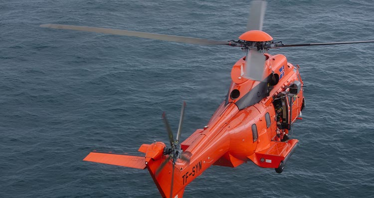 An orange helicopter flies over the open ocean.