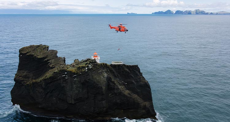 A helicopter hovers a small island with a lighthouse on it.