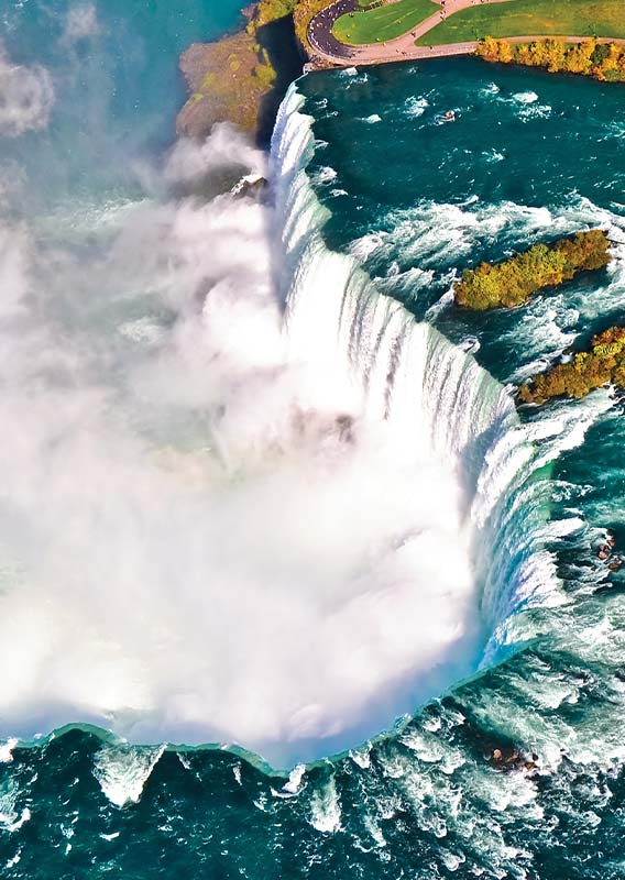 A birds-eye view of Niagara Falls, a wide curved waterfall with lots of mist below the falls.