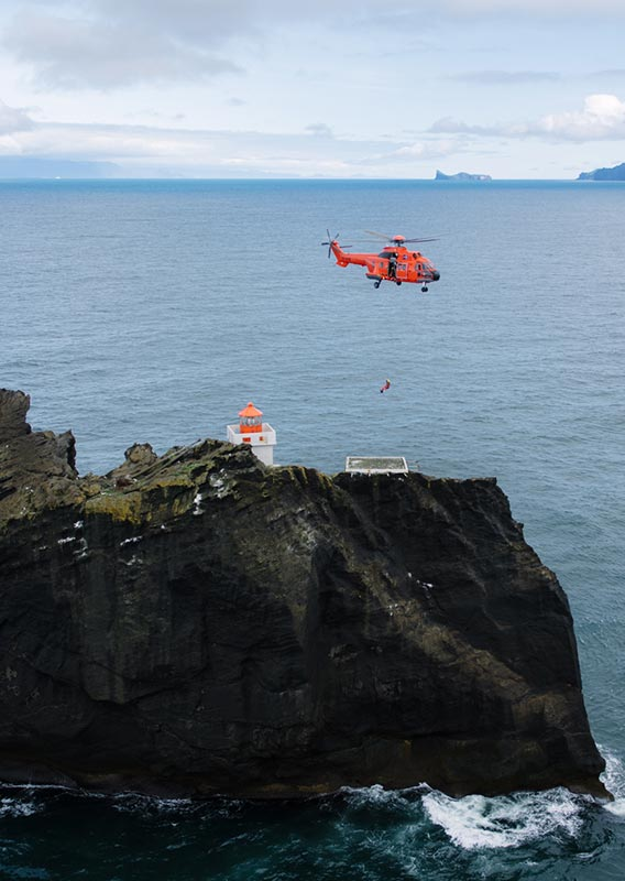 A helicopter hovers above a small island and lighthouse.